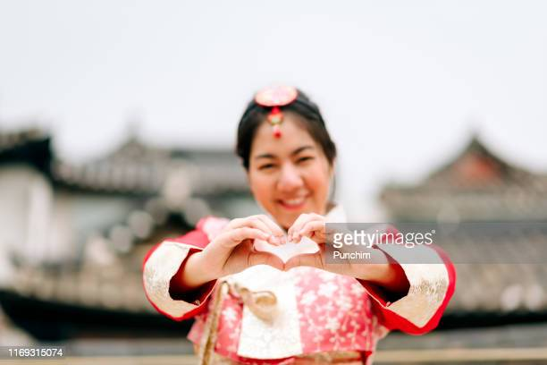 asian woman dressed hanbok showing heart sign in seoul, south korea - korea stock pictures, royalty-free photos & images