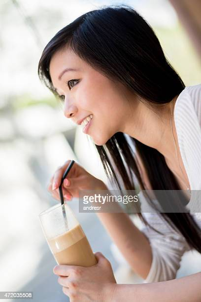 Asian woman drinking a frappuccino at a cafe
