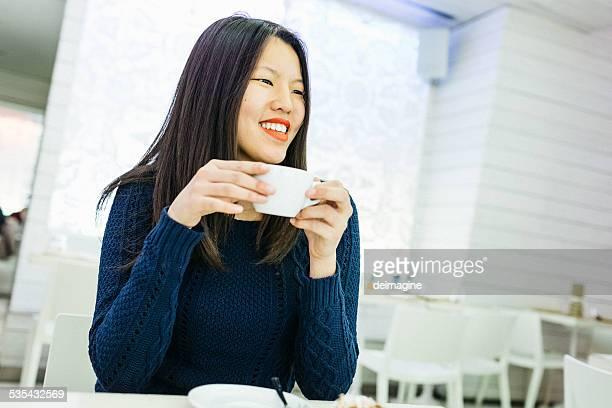 アジア人の女性がコーヒーを飲む