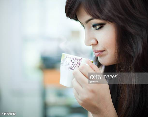 Asian woman drinking hot, steaming tea or coffee.