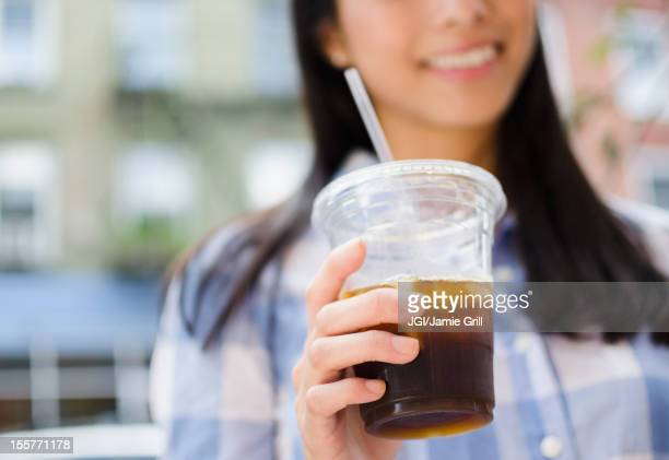 Asian woman drinking iced coffee