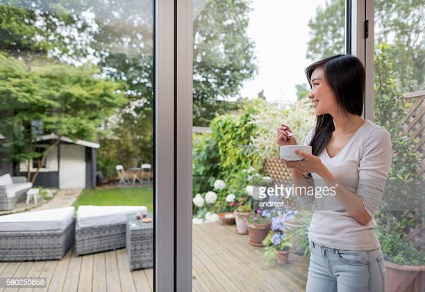 Asian woman eating breakfast at home