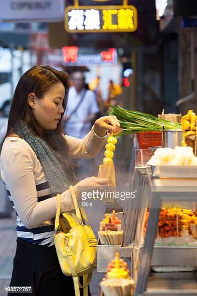 Asian woman eating Hong Kong street food