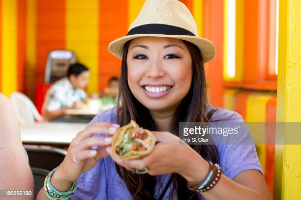 Asian woman eating in restaurant