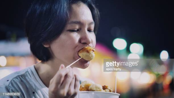 asian woman eating meatball at night market - one night stand stock-fotos und bilder