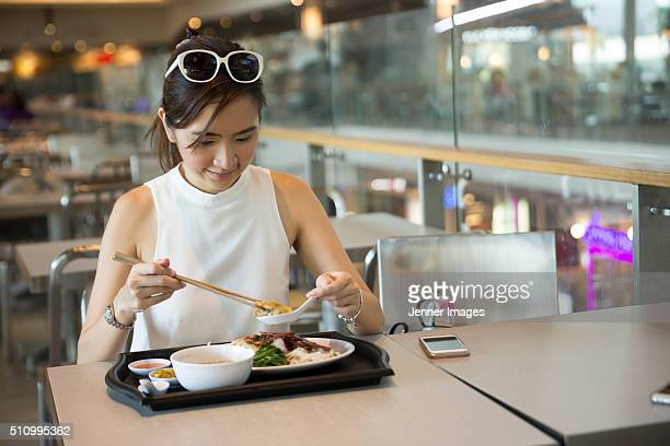 Asian Woman eating noodles for lunch
