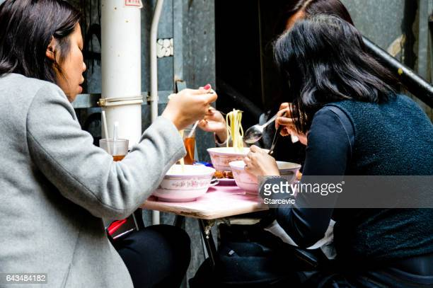 Asian woman eating on streetside cafe