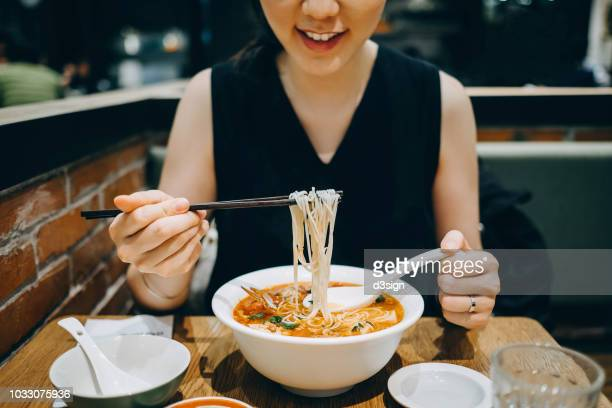asian woman eating soup noodles joyfully in restaurant - pho soup stock pictures, royalty-free photos & images