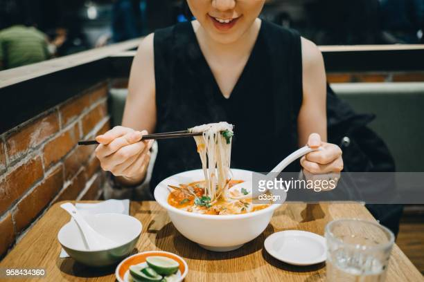 asian woman eating soup noodles joyfully in restaurant - traditionally vietnamese stock pictures, royalty-free photos & images