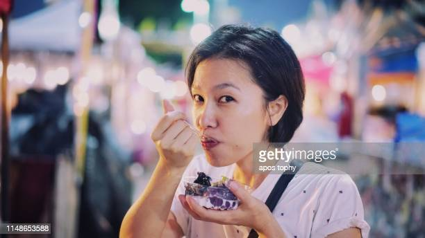 asian woman eating street food at night market - one night stand stock-fotos und bilder
