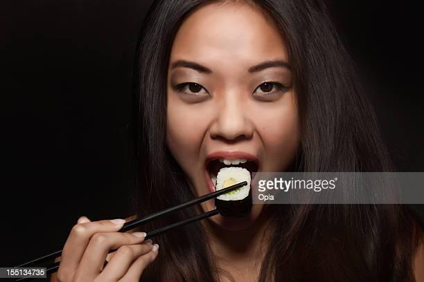 Asian woman eating sushi maki