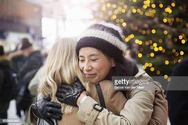 asian woman embraces friend in railroad station, christmas tree in background. - christmas scenes stock photos and pictures