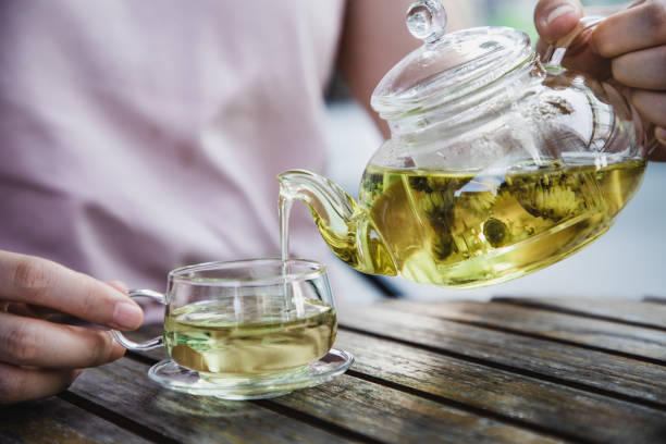 asian woman enjoy a cup of herbal tea - herbal tea stock pictures, royalty-free photos & images
