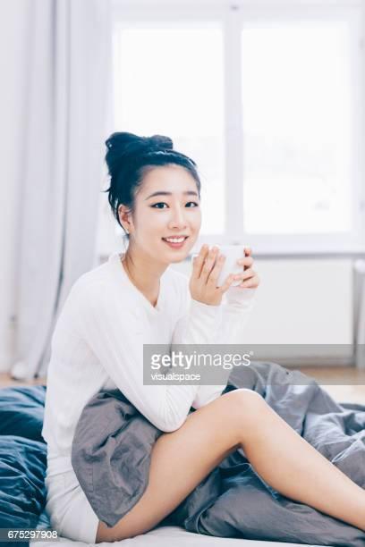 Asiatische Frau, die ihren Morgenkaffee genießen