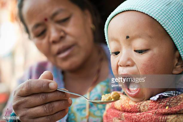 Asian woman feeding food to little child.