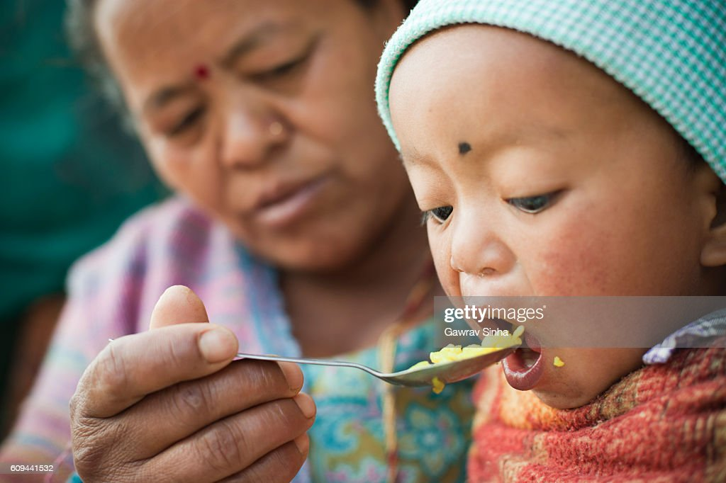 Asian woman feeding food to little child. : Stock Photo
