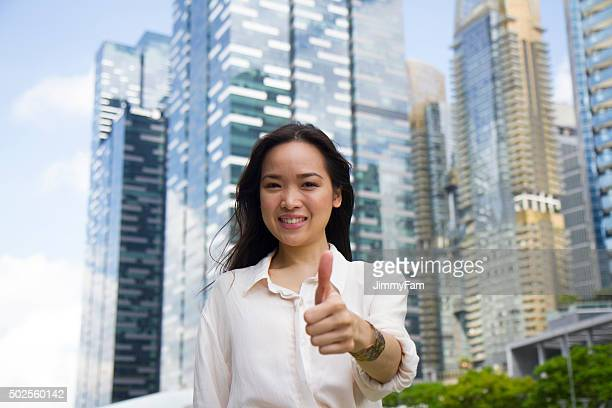 Asian woman giving one thumbs up sign
