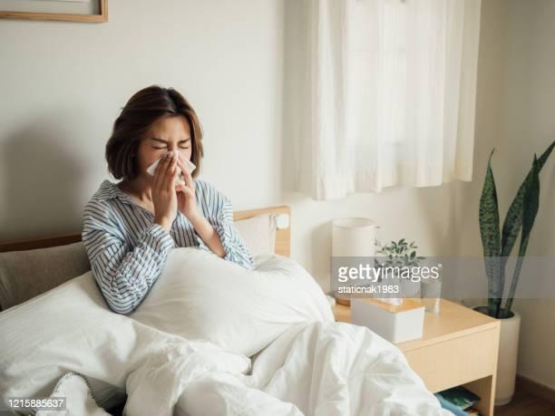 aziatische vrouw kreeg griep niezen in weefsel zitten op bed - verkoudheid en griep stockfoto's en -beelden