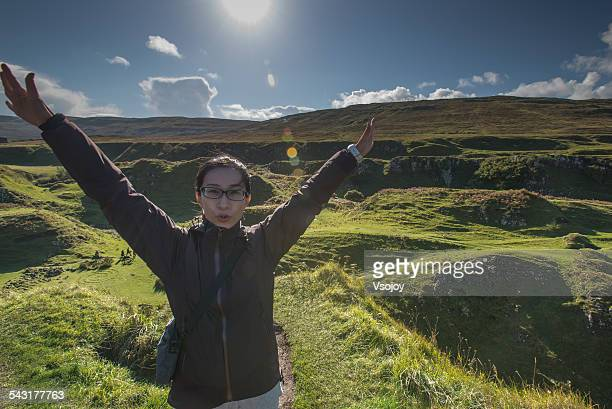 asian woman hands in the air at fairy glen, skye - vsojoy stock pictures, royalty-free photos & images