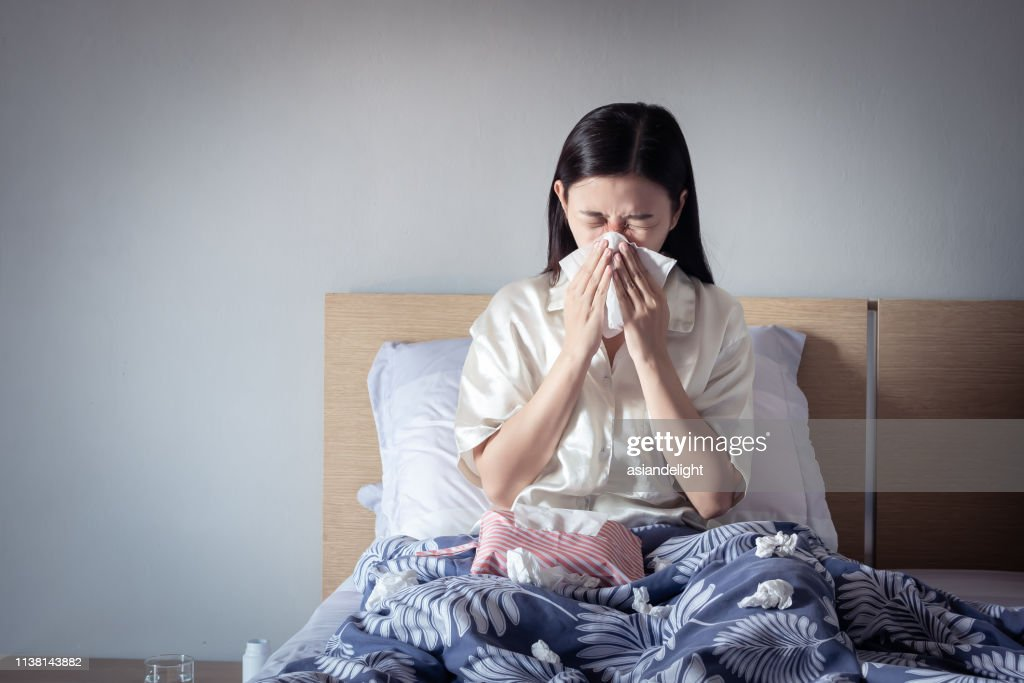 Asian woman have a cold, sitting on cozy bed using tissue for snot. sick at home : Stock Photo