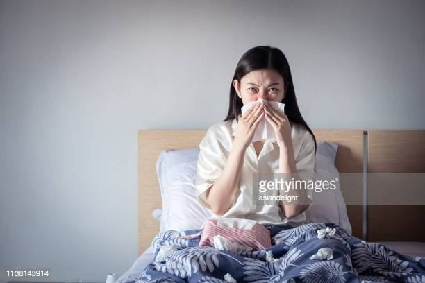 asian woman have a cold, sitting on cozy bed using tissue for snot. sick at home - mucus stock pictures, royalty-free photos & images