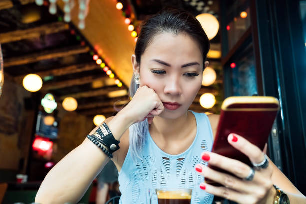 asian woman having bad news on mobile phone - furious asian woman stock pictures, royalty-free photos & images