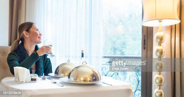 Asian woman having dinner in a luxury five stars hotel room