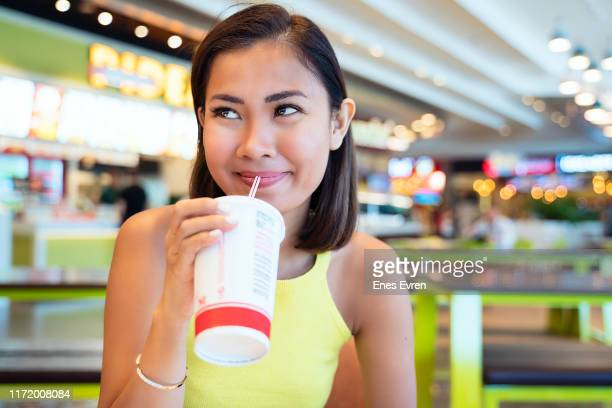 asian woman having fast food, drinking with disposable cup in shopping mall food court - fast food stock pictures, royalty-free photos & images