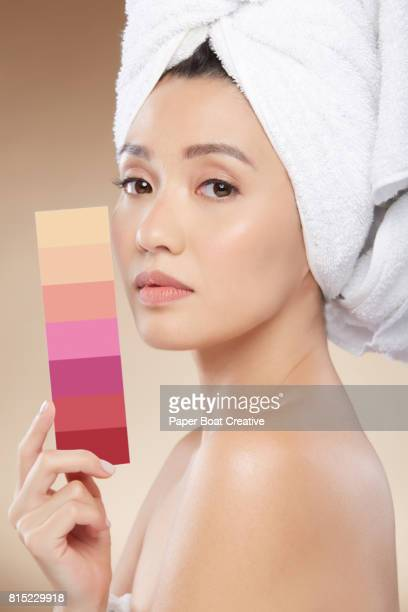 Asian woman holding a color palette of the different colors and shades of lipstick she uses