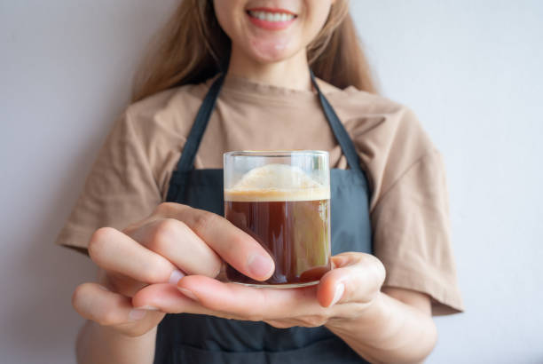 Asian woman holding a cup of espresso coffee.