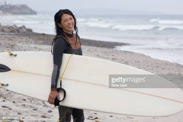 asian woman holding a surfboard on the beach - asian 50 to 55 years old woman stock photos and pictures