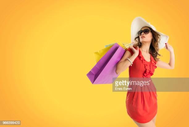 asian woman holding fancy shopping bags on orange background - saldi foto e immagini stock