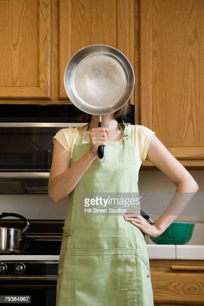 Asian woman holding frying pan in front of face