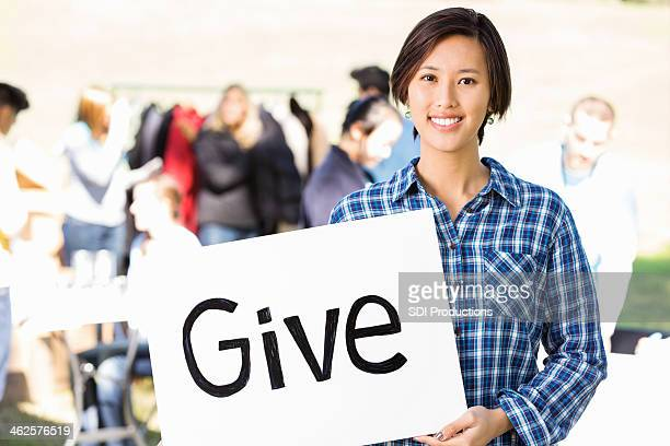Asian woman holding ''give'' sign at outdoor donation event
