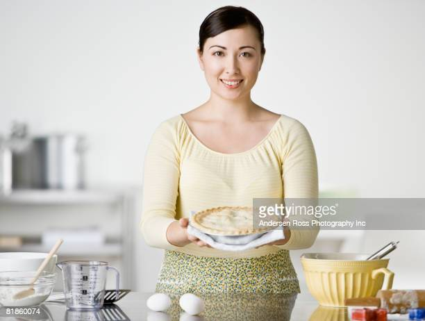asian woman holding homemade pie - homemaker stock pictures, royalty-free photos & images