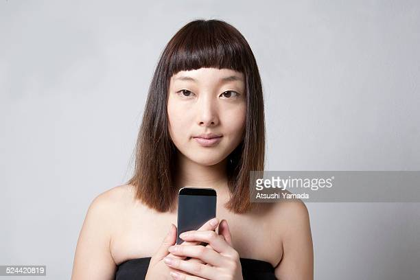 Asian woman holding mobile phone in hand
