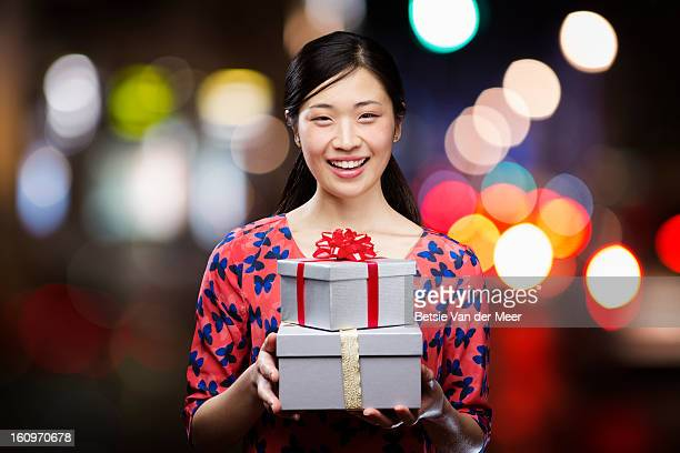 Asian woman holding presents,smiling.