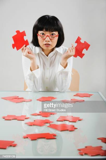 Asian woman holding puzzle pieces