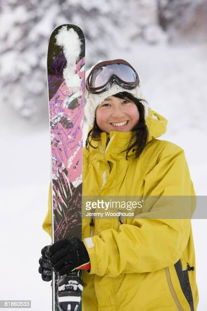 Asian woman holding skis