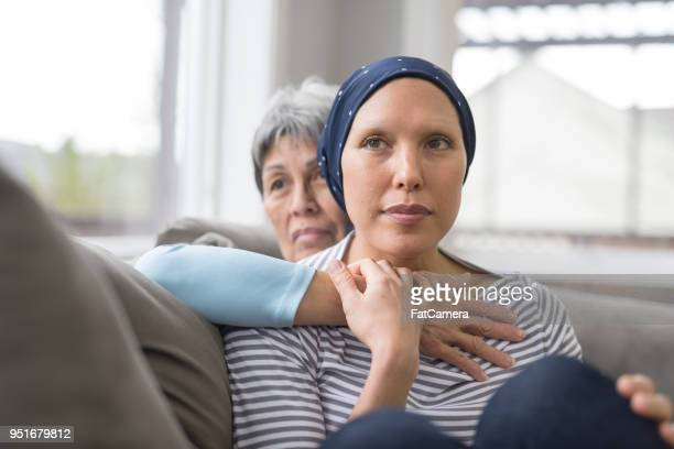 Asian woman in 60s sitting on couch and embracing her mid-30s daughter who is fighting cancer