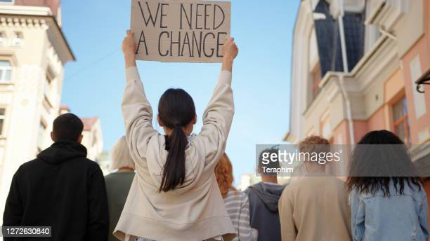 asian woman in back of protest demonstration holding a poster we need a change. student activist - slogan stock pictures, royalty-free photos & images