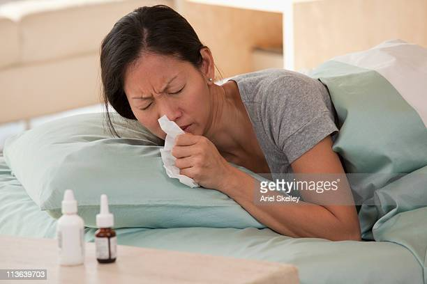 Asian woman in bed with the flu