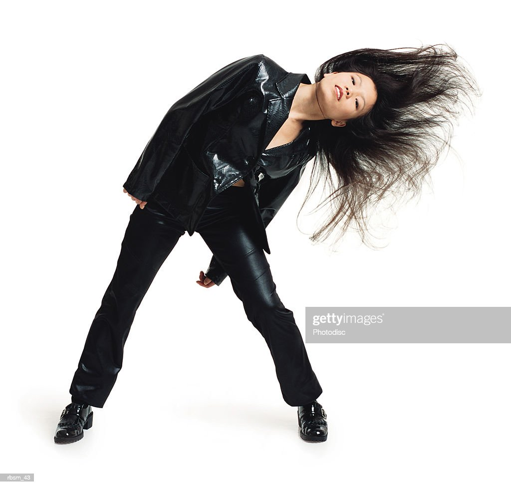 asian woman in black leather pants and jacket swinging head to the side with hair flowing : Foto de stock