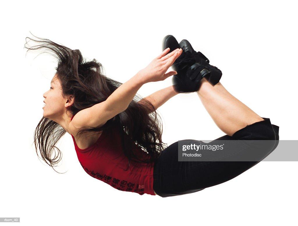 asian woman in black pants and red shirt jumping up and arching back to grab her legs : Foto de stock