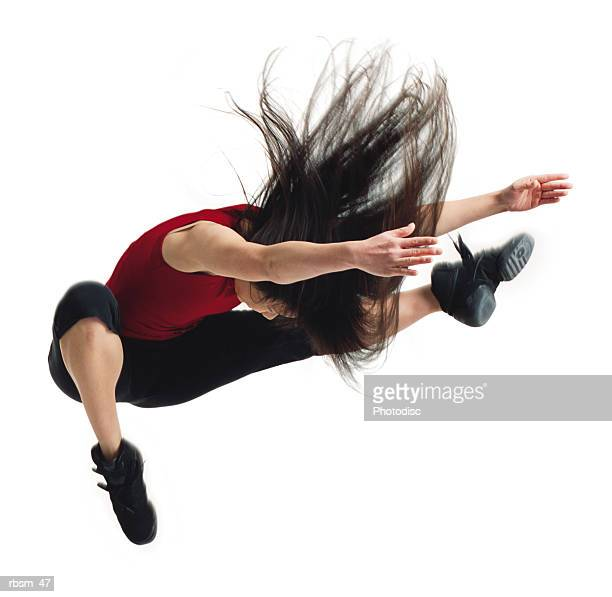 asian woman in black pants and red shirt jumping with arms and legs forward and hair flowing - clubkleding stockfoto's en -beelden