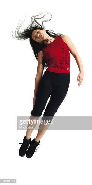 asian woman in black pants and red shirt jumping with legs together leaning to the side with hair flowing - clubkleding stockfoto's en -beelden