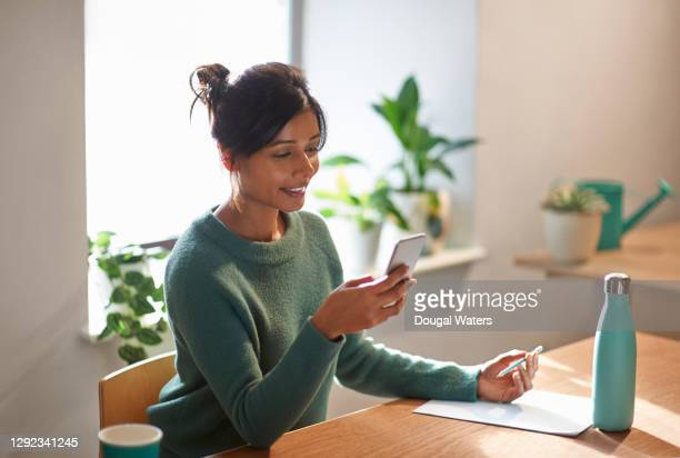 asian woman in green jumper checking mobile at home desk. - telephone stock pictures, royalty-free photos & images