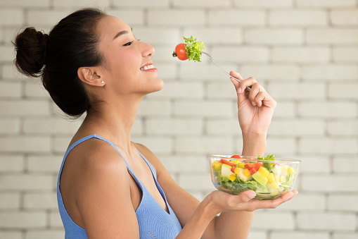 Asian woman in joyful postures with salad bowl on the side 1090509610
