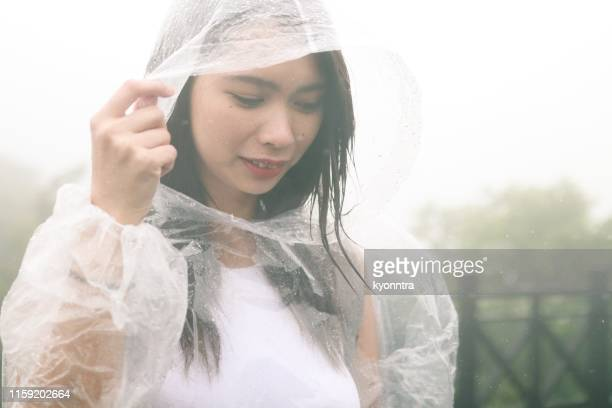 asian woman in raincoat - poncho stock pictures, royalty-free photos & images