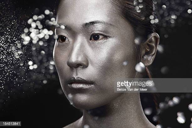 asian woman in silver with sparkles in air. - east asian ethnicity stock pictures, royalty-free photos & images